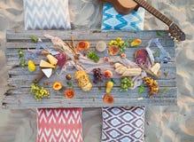 Tome parte num piquenique na praia no por do sol no estilo do boho, alimento e beba concentrado fotografia de stock royalty free