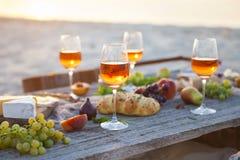 Tome parte num piquenique na praia no por do sol no estilo do boho, alimento e beba concentrado fotografia de stock