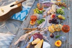 Tome parte num piquenique na praia no por do sol no estilo do boho, alimento e beba concentrado fotos de stock royalty free
