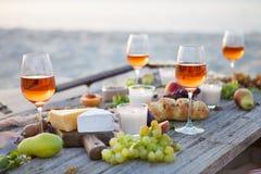 Tome parte num piquenique na praia no por do sol no estilo do boho, alimento e beba concentrado fotos de stock