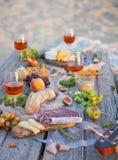Tome parte num piquenique na praia no por do sol no estilo do boho, alimento e beba concentrado foto de stock