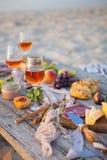 Tome parte num piquenique na praia no por do sol no estilo do boho, alimento e beba concentrado imagem de stock royalty free