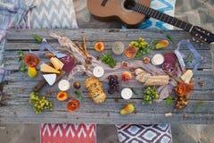 Tome parte num piquenique na praia no por do sol no estilo do boho, alimento e beba concentrado foto de stock royalty free