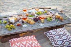 Tome parte num piquenique na praia no por do sol no estilo do boho, alimento e beba concentrado imagens de stock