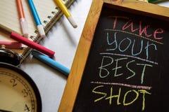Tome seu melhor tiro em escrito à mão colorido da frase no quadro, no despertador com motivação e nos conceitos da educação fotos de stock royalty free