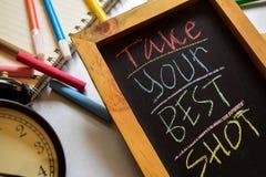 Tome seu melhor tiro em escrito à mão colorido da frase no quadro, no despertador com motivação e nos conceitos da educação fotos de stock