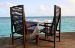 Tome um assento - duas cadeiras da madeira escura em uma tabela a Imagem de Stock Royalty Free