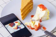Tome um bolo doce com um telefone imagem de stock royalty free