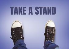 Tome um texto do suporte e umas sapatas pretas nos pés com fundo roxo Imagem de Stock Royalty Free