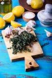 Tomilho, limões e alho frescos na placa de madeira Imagem de Stock
