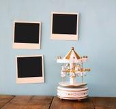 Tomma ögonblickliga foto hänger över trätexturerad bakgrund bredvid vita karusellhästar för tappning Royaltyfri Foto