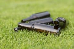 Tomma ölflaskor i gräset Arkivfoton
