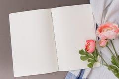 Tomma ark av den öppna anteckningsboken på en blå bakgrund arkivfoton