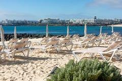 Tomma chaise-vardagsrum på stranden i staden av Costa Teguise royaltyfri bild