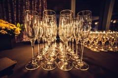 Tomma champagneexponeringsglas i rad på aftonhändelsepartiet som väntar på gästerna arkivfoton