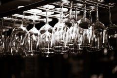Tomma exponeringsglas för vin ovanför en stång rack royaltyfri bild