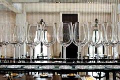 Tomma exponeringsglas för vin ovanför en stång rack Royaltyfria Bilder