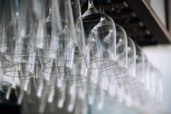Tomma exponeringsglas för vin ovanför en stång rack hänga Royaltyfria Bilder