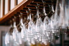 Tomma exponeringsglas för vin ovanför en stång rack Hängande vinexponeringsglas in Royaltyfria Foton