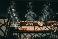 Tomma exponeringsglas för vin ovanför en stång rack i tappning Fotografering för Bildbyråer