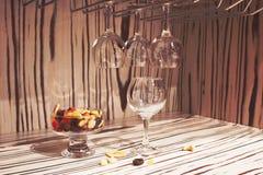 Tomma exponeringsglas för vin ovanför en stång rack torkade frukter Royaltyfri Bild