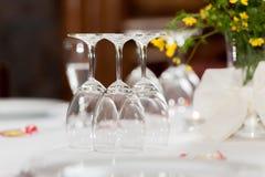 Tomma exponeringsglas på tabellen i restaurang med blom- garnering royaltyfria foton