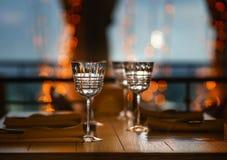 Tomma exponeringsglas står mot bakgrunden av aftonhimlen i ett kafé, mot bakgrunden av en bokeh royaltyfri foto