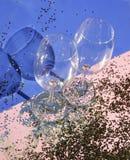 Tomma exponeringsglasbägare för champagne i guld- konfettier på tabellen festlig bakgrund Champagne med den isolerade flygballong royaltyfria bilder