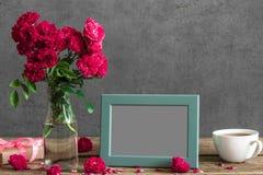 Tomma fotoram- och rosblommor med kopp te- och gåvaasken på den lantliga trätabellen Åtlöje upp 1 livstid fortfarande royaltyfri fotografi