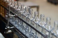 Tomma glasflaskor på transportören Fabrik för att buteljera alkoholdrycker arkivfoto