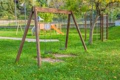 Tomma gungor på lekplatsen för barn nära barntrappa glider utrustning Royaltyfri Foto