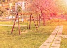 Tomma gungor på lekplatsen för barn nära barntrappa glider utrustning på solnedgångstrålljus Arkivbild