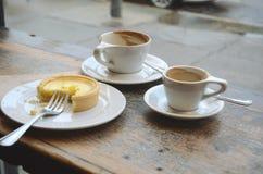 Tomma kaffekoppar och ett oavslutat syrligt på en tabell i en coffee shop Royaltyfria Foton