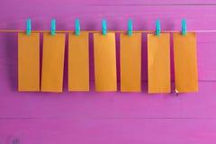 Tomma orange anteckningsbokark som hänger från rad Arkivbild