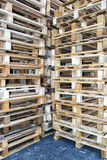 Tomma paletter som staplas i ett lager Arkivfoto