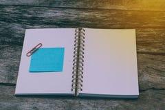Tomma pappers- arkblått med den tomma anteckningsboken på träbakgrund Fotografering för Bildbyråer