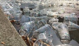 Tomma plast- koppar som skräpar ner gatan under en maraton royaltyfri bild