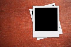 Tomma polaroid- fotoramar på skrivbordet Arkivbilder