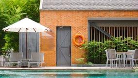 Tomma poolsidedagdrivare med paraplyer Fotografering för Bildbyråer