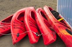Tomma röda plast- fritids- kajaker för hyra eller hyra som lagras på den sandiga stranden efter timmar på en regnig dag Crescent  royaltyfria foton