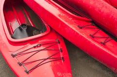 Tomma röda plast- fritids- kajaker för hyra eller hyra som lagras på den sandiga stranden efter timmar på en regnig dag Crescent  arkivbild