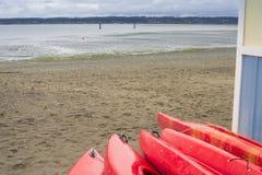 Tomma röda plast- fritids- kajaker för hyra eller hyra som lagras på den sandiga stranden efter timmar på en regnig dag Crescent  royaltyfri fotografi