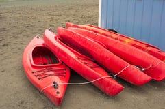 Tomma röda plast- fritids- kajaker för hyra eller hyra som lagras på den sandiga stranden efter timmar på en regnig dag Crescent  Royaltyfri Foto