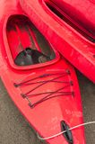 Tomma röda plast- fritids- kajaker för hyra eller hyra som lagras på den sandiga stranden efter timmar på en regnig dag Crescent  Royaltyfri Bild