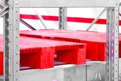 Tomma röda plast- paletter på kuggar i ett komplex för automatiserat lager arkivfoton