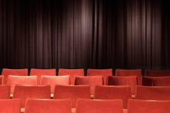 Tomma röda stolar på teatern Arkivbilder