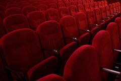 Tomma rader av röda teater- eller filmplatser, sidosikt Arkivbilder