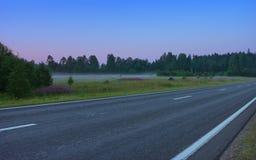 Tomma raka Asphalt Road In en Misty Morning Twilight arkivbild
