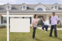 Tomma Real Estate undertecknar och den latinamerikanska familjen framme av huset Arkivfoton