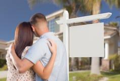 Tomma Real Estate undertecknar och militära par som ser huset Royaltyfri Foto